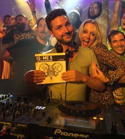 DJ in club with dancer and IQ-ME colouring book in his hands