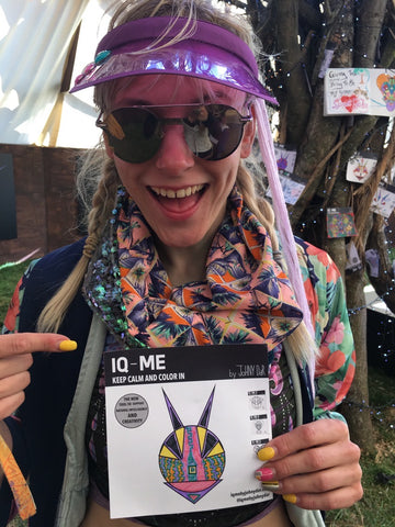 smiling girl with sunglasses and a purple gap with IQ-ME art piece in her hands at a festival