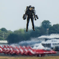 A man in a jetsuit hovers over the ground