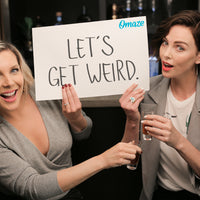 A photo of June Raphael and Charlize Theron holding a sign reading, 'Let's get weird!'