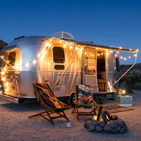 An Airstream Flying Cloud at night with string lights illuminating two camping chairs