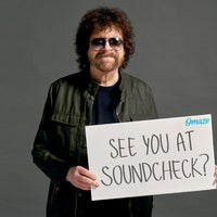 Jeff Lynne holds a white sign that reads See You At Soundcheck?