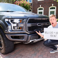 J.J. Watt holding a sign reading, 'New Car + House. You In?' and posing in front of a black Ford F-150 Raptor