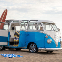 An exterior shot of the blue and white 1967 VW 21-Window Bus, on the beach