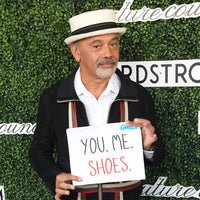 Christian Louboutin holds a sign that reads You. Me. Shoes.