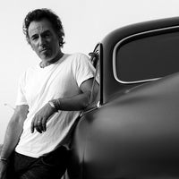 Bruce Springsteen leaning against his car in Asbury Park, NJ