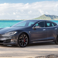 A silver Tesla S Performance parked on a beach in Hawaii