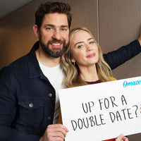 John Krasinski and Emily Blunt hold a sign that reads