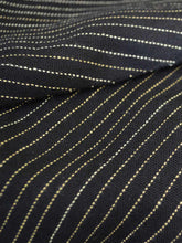 Load image into Gallery viewer, Close up view of the material of Front view of hanger shoot of Black and gold stripe tiered jacket designed by Khumanthem Atelier