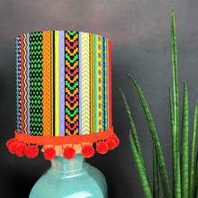 Load image into Gallery viewer, Multi-stripe fabric with mirror copper liner and optional orange pompom lampshade