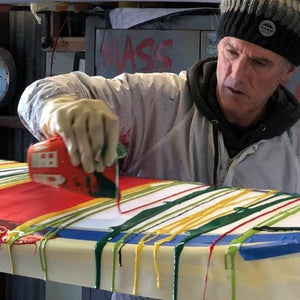 Dave Moore of DMZ Surfboards pouring colored resin on a custom surfboard glass job
