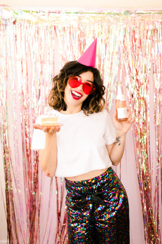 Girl in sequins with cake and champagne