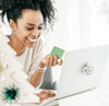 Woman holding gift card while browsing laptop