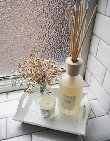 Reed diffuser on tray in bathroom
