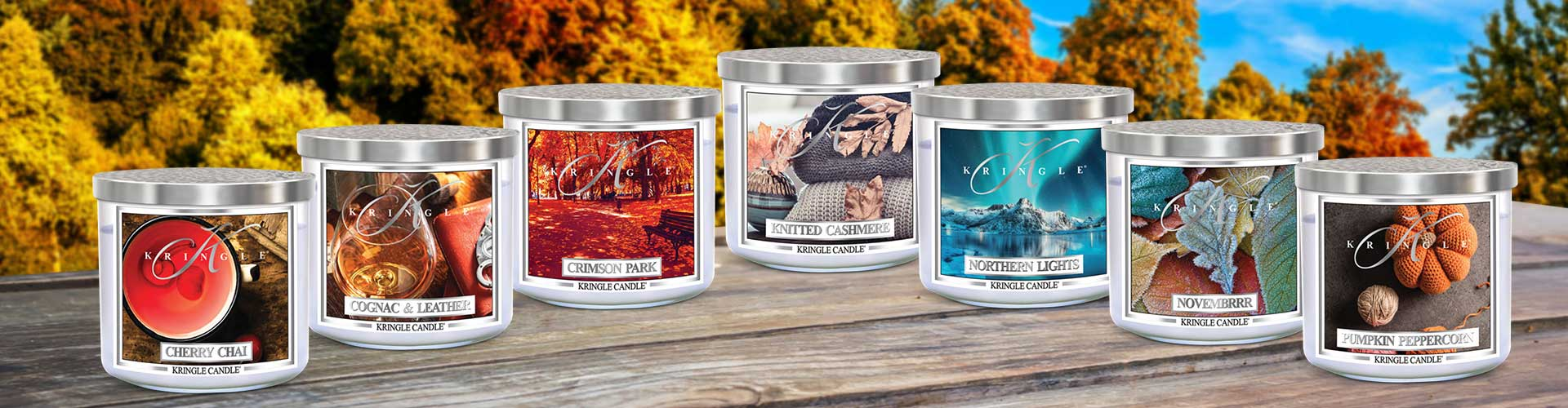 Graphic showing an assortment of Kringle Candle's Candle Tumblers sitting on a picnic table with hot air balloons in the background.