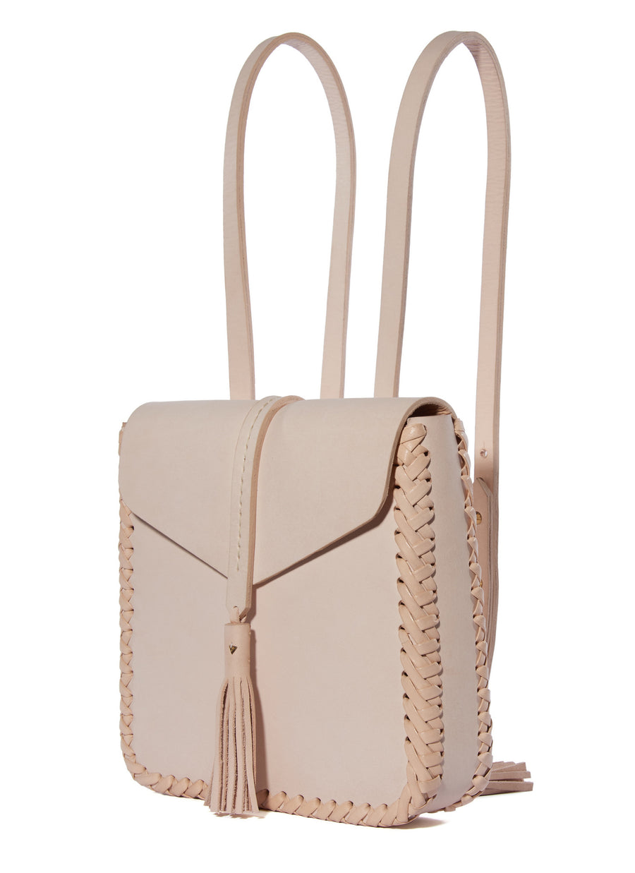 Natural Pink Tan Eco Leather Saddle Envelope Closure Flap Small Tiny Mini Backpack Wendy Nichol Designer Handbag Bag Purse Handmade in NYC New York City Adjustable Strap Fringe Tassel Tassels Structured Structure Square Braided edges interior pocket durable Cher Clueless