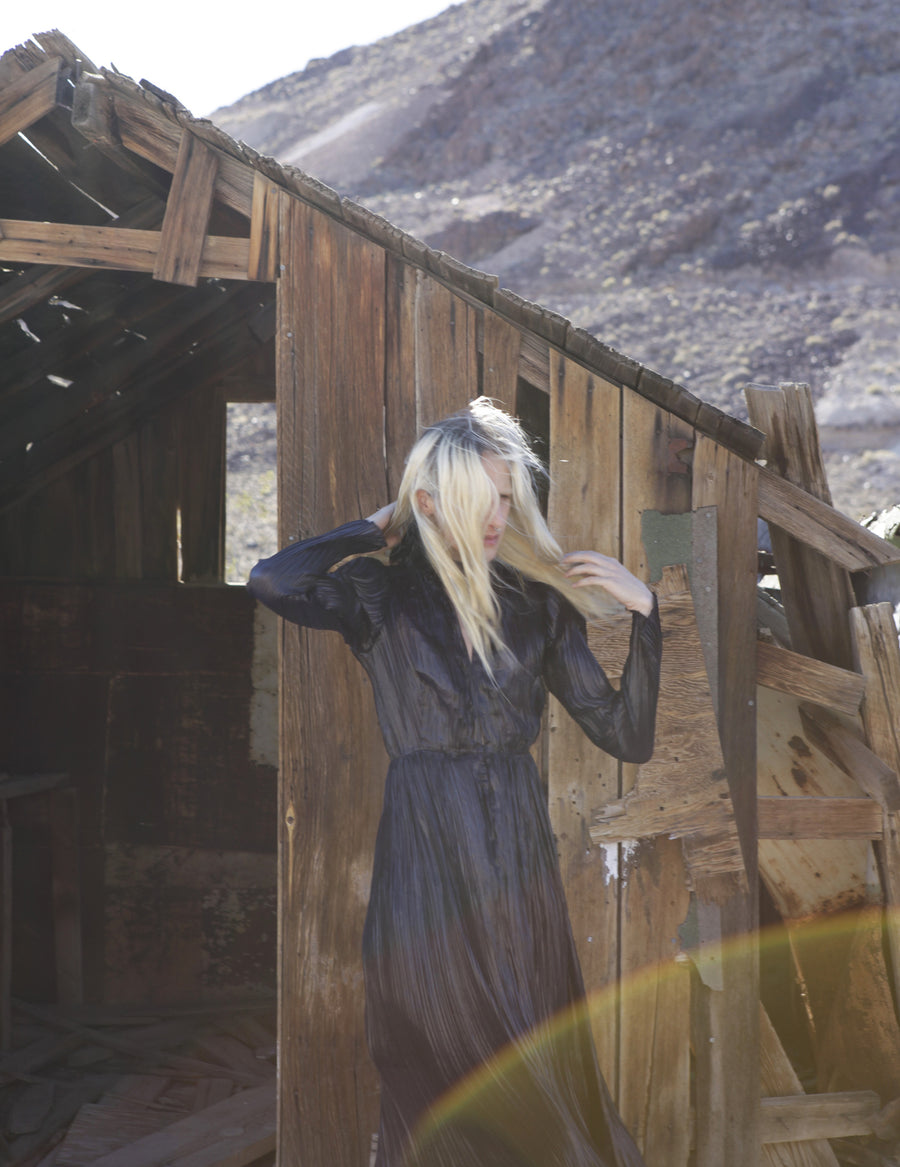 Ryan James Smith model Sheer Sparkle Midnight Navy Blue Dress Long Sleeves High Collar Victorian Edwardian Future lines pleated pleats silk Wendy Nichol Clothing Designer SS17 Ready to Wear Fashion Runway Show Death Valley Desert Mirror Patent Metallic Silver Emerald shape Clutch leather bag Handmade in NYC
