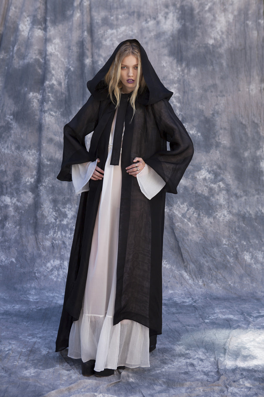 Maggie Laine IMG model Wendy Nichol New York Clothing Designer Handmade in NYC New York City SS17 Fashion Runway Show Signals to the Mothership Made to Order Custom Tailoring Made to Measure Death Valley Black Sheer Hood Hooded Cape Cloak Coat Belle Sleeves Long Train Oversized Hood White Sheer Apron Cross Tie Pleated Sleeves Dress Victorian Edwardian Gothic Goth Pagan Witch High Priestess Sorceress Magician Wizard