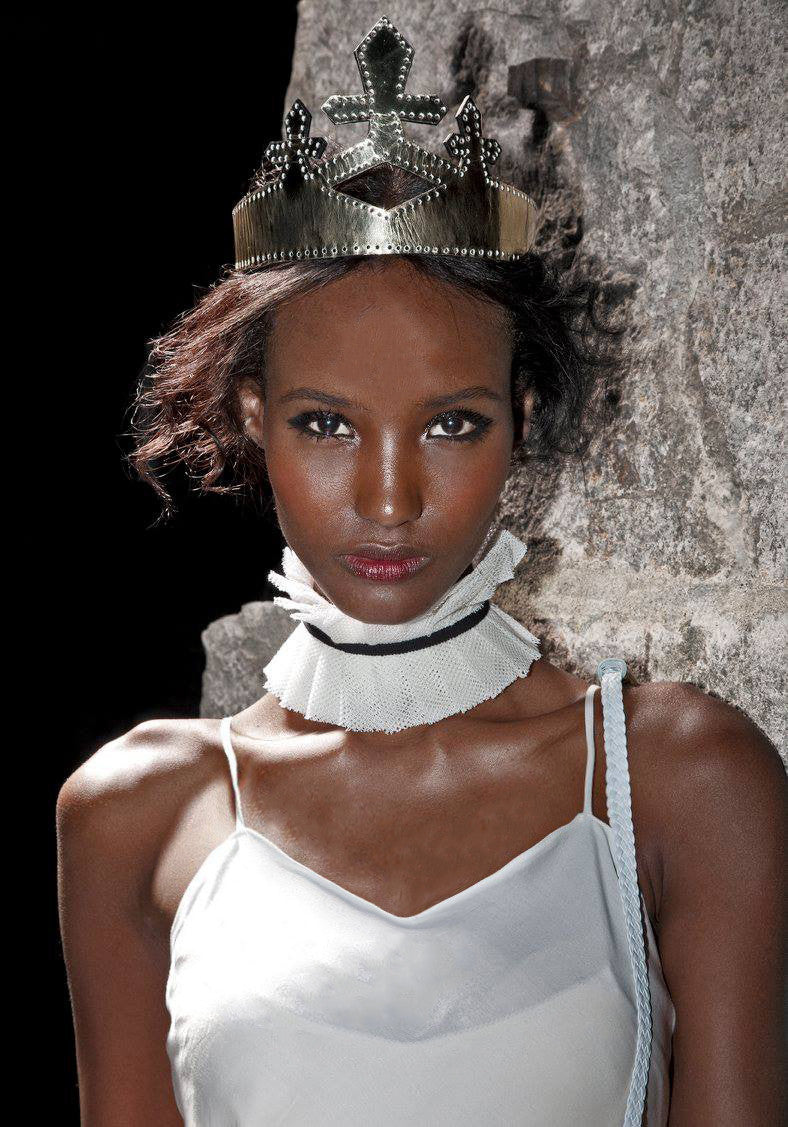 Fatima Siad IMG Model Wendy Nichol Clothing Designer Ready to Wear Fashion Runway Show SS14 Saints of the Zodiac Astrological Sign Leo the Lion White Bias Cut Long Train White Net Tulle Inserts Panels Cut Out strap Cotton Silk White Ruffle Edwardian Collar with Black Ribbon Gold Black Patent Leather Queen Crown Handmade in NYC New York City made to Measure Order Custom Tailoring Fabric Color