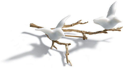 a brooch with two porcelain pigeons