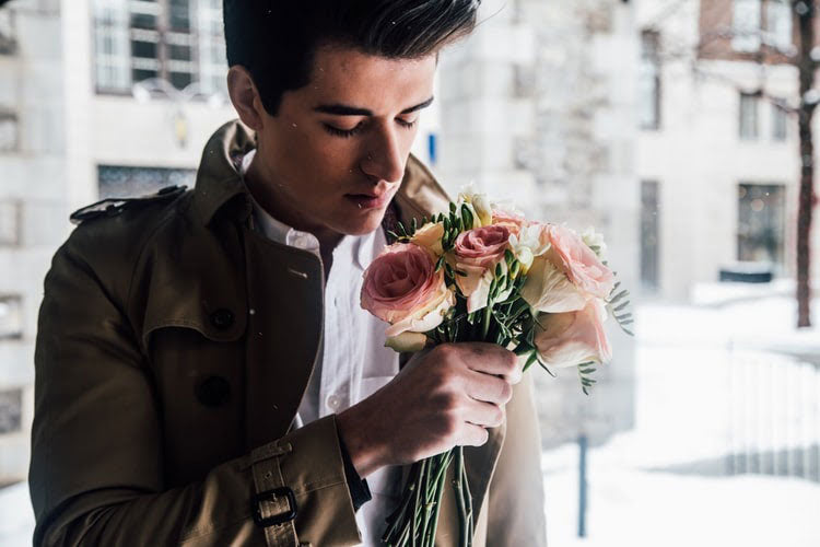 a man holds a bouquet of roses
