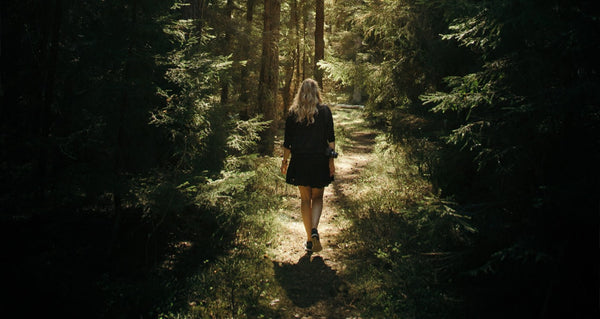 Woman walking in forest with camera