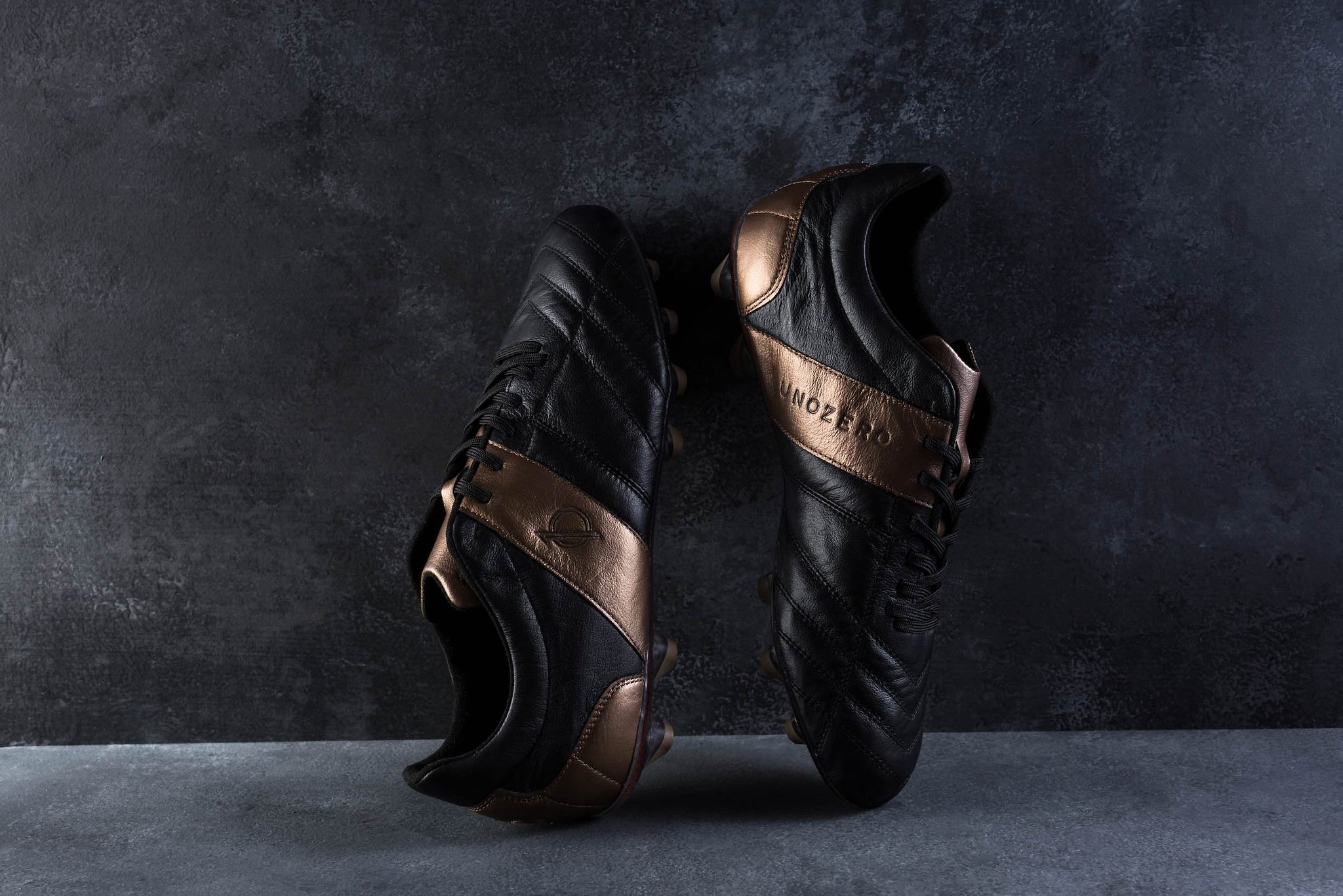 Black and gold leather cleats against wall