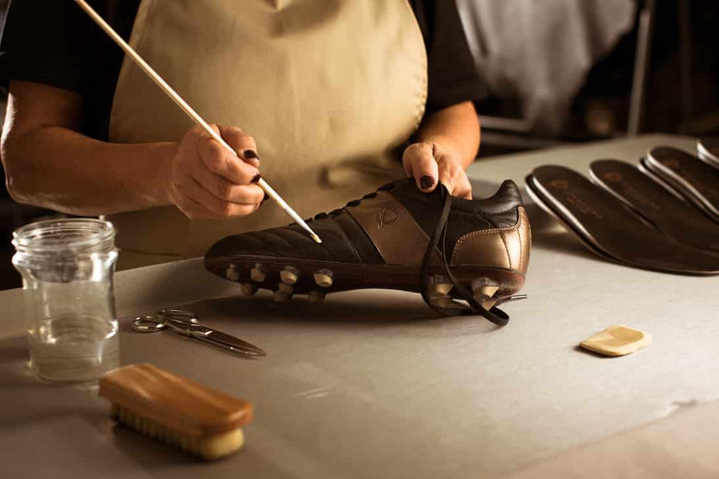 Shoemaker with leather brush working on custom shoes