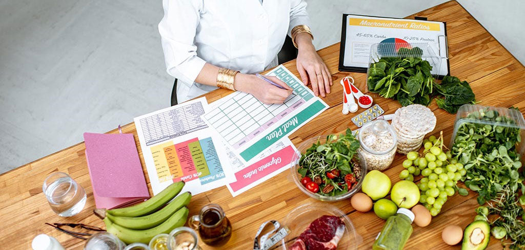 Nutritionist surrounded by fruit and veg at desk