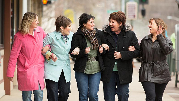Five women in winer coats walking arm in arm down street