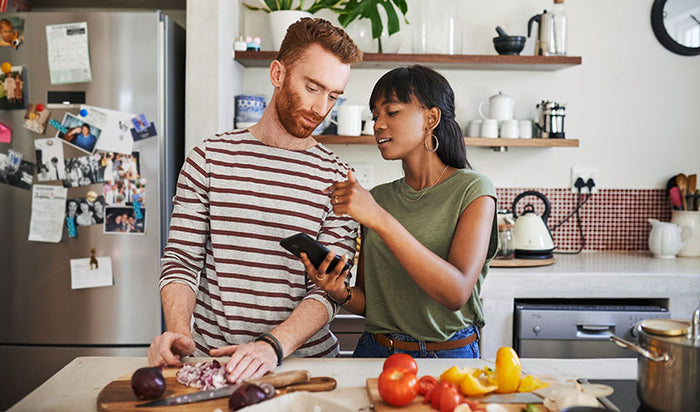 young woman using her cellphone while cooking with her boyfriend at home at home