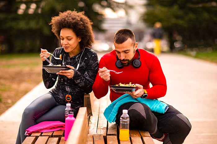 Young athletic couple in sports clothing sitting side by side on a park bench, enjoying a healthy vegan meal together.
