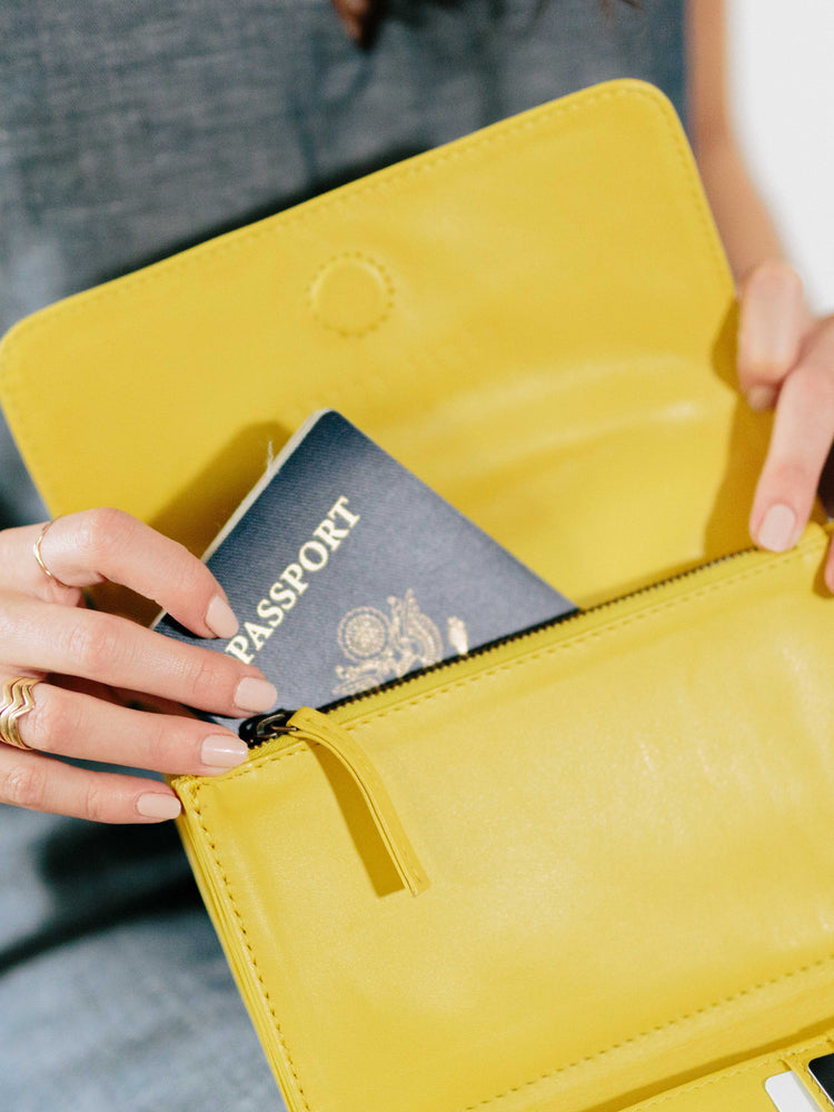 Travel wallet payton james- model holding wallet with passport showing-yellow passport wallet payton James