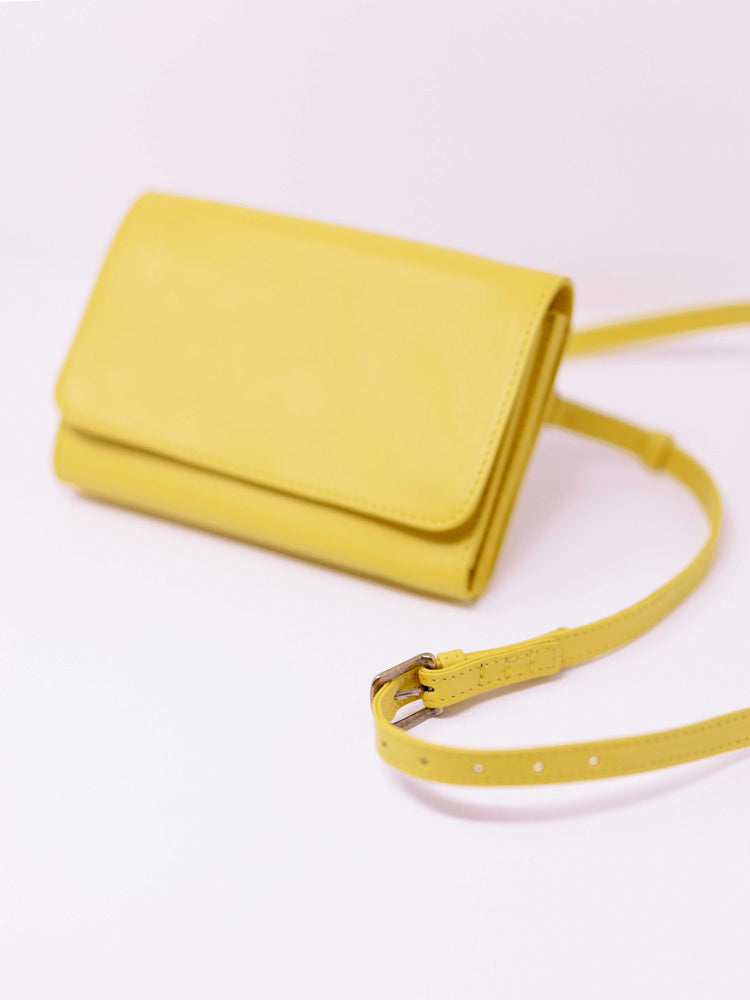 Yellow crossbody travel wallet with strap showng by payton james