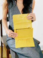Travel wallet by payton james- model holding the inside of the yellow travel wallet