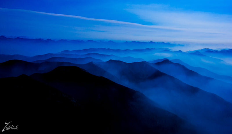 aerial photograph by Zedekiah overlooking a mountain range with a misty fog. Colors are mostly blue with white clouds and black shadows