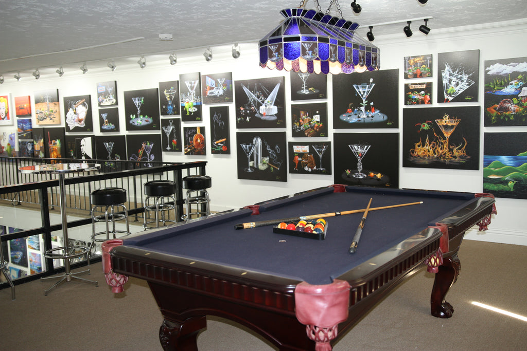 Interior view of artwork display inside RockStars of Art gallery game room with pool table and Michael Godard art and merchandise