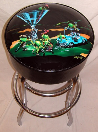 "Black leather Bar Stool with chrome legs. A martini glass with ""19th Hole"" on the stem sits on the green of a golf course. A light teal golf cart next to the glass has two olives hanging out on top of it. Four olives, two female, two male drink their martinis and wave their golf clubs around, while a female olive sits on top of the glass holding the red flag."