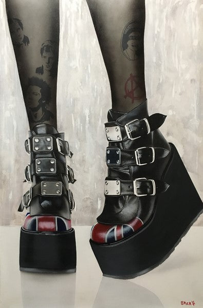 A woman's legs are pictured from the calves down. Behind some dark translucent tights are multiple tattoos, from a face of Elvis to a red anarchy emblem. She is wearing black platform heels with several metal buckles and a red pattern on the toe, all on a white and gray background.