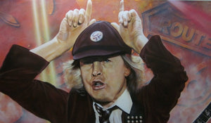 Angus Young is pictured holding his hands over his head in a horn motion. He is wearing a maroon suit and baseball hat, as well as a patterned tie. The background is a rust color with a sign reading Route 66.