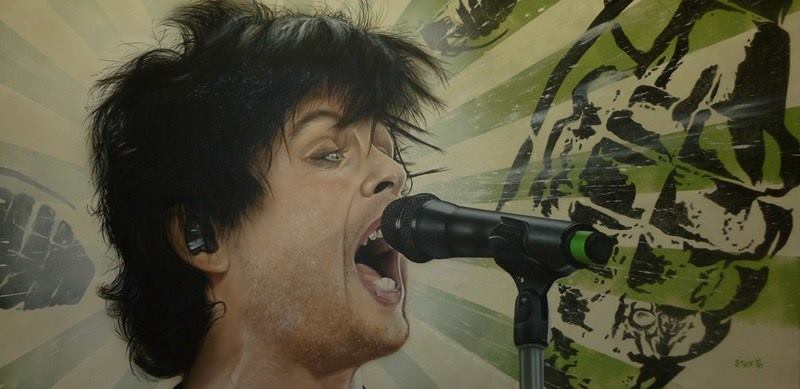 Billie Joel Armstrong of Green Day is pictured from the neck up, expressively singing into a microphone on a stand. A green and white striped background is printed with several black grenades.