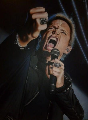 Billy Idol is shown from the waist up from a lower angle. He is wearing all black and has multiple rings and other articles of silver jewelry. His face is scrunched as he is yelling into a microphone in his hand. There is a black background with some thin white lights shining across it.