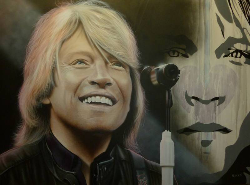 Bon Jovi is pictured with a wide smile on his face, looking in the distance. He is wearing a black leather jacket and a microphone on a white stand is in front of him. In the background is a painted image of his face in various shades of gray.