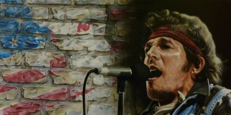 A slightly blurred Bruce Springsteen is shown from the shoulders up, facing towards the left, singing passionately into a microphone, wearing a red bandana around his forehead and a heavy jacket. In the background are white bricks and on the left a faded spray paint American flag.