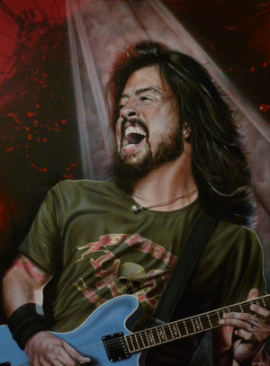 Dave Grohl from Foo Fighter is pictured from the hips up, slightly angled left. He is wearing a green and red shirt with skulls and crossbones on it, and is holding a blue electric guitar. He's got a wide, open mouthed smile on his face. In the background is a red and black splash with a white spotlight.