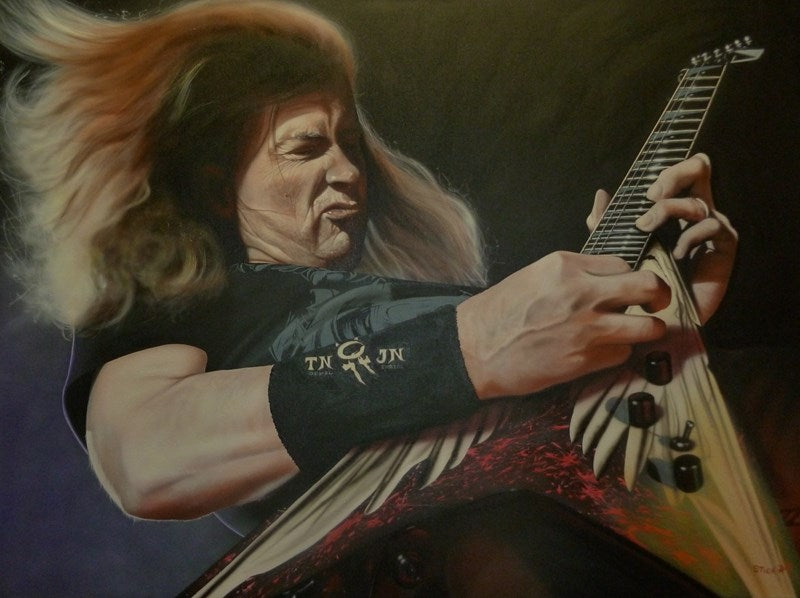 "Dave Mustaine is shown passionately playing the guitar. He is wearing a black t-shirt and his hair is flying behind him as he presumably is sliding across the floor.The guitar is triangular and red, with white angel wings on it. The sweatband on his wrist reads ""TN JN."""