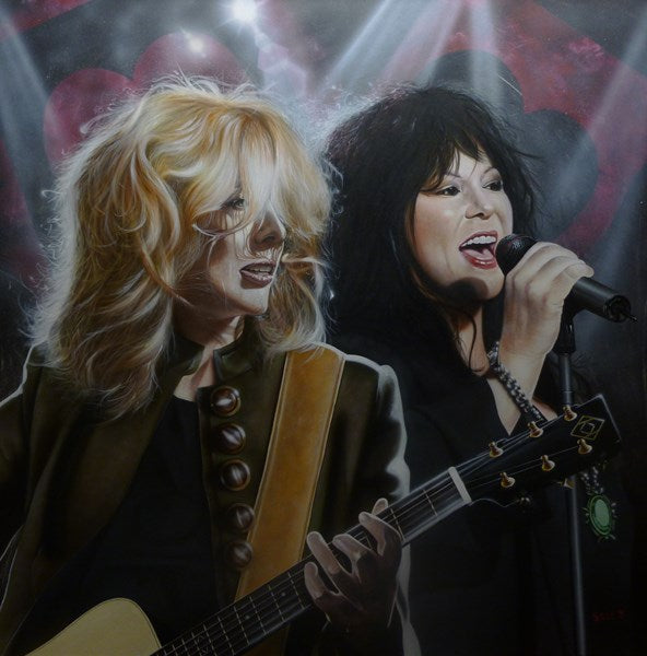 Ann and Nancy Wilson are pictured on stage. Nancy Wilson is playing guitar in a buttoned green jacket and a black undershirt. Ann is singing into a microphone with a black jacket. Lights flash in a background with black and red hearts.