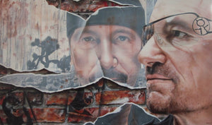 """Bono"" from U2 is pictured on the right side, facing left, wearing glasses and a blank stare. In the background are bricks with black spraypaint showing the other members of the band. Also in the back is a large broken mirror with ""The Edge's"" face in it, wearing a beanie."