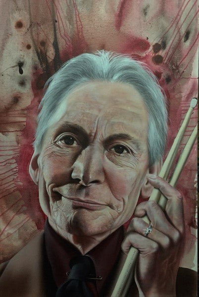 Charlie Watts from Rolling Stones is shown from the chest up in a maroon suit smiling slightly, with a pair of drumsticks in his raised hand. The background shows splashes of reds and black in a water-color moving outwards from his face.