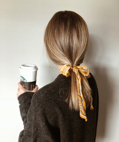 back-of-woman's-head-hair-tied-in-low-pony-with-yellow-ribbon